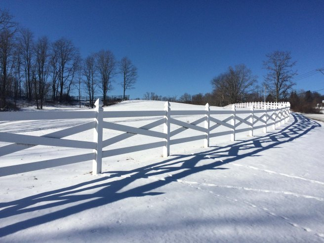 white fence and snow shadows